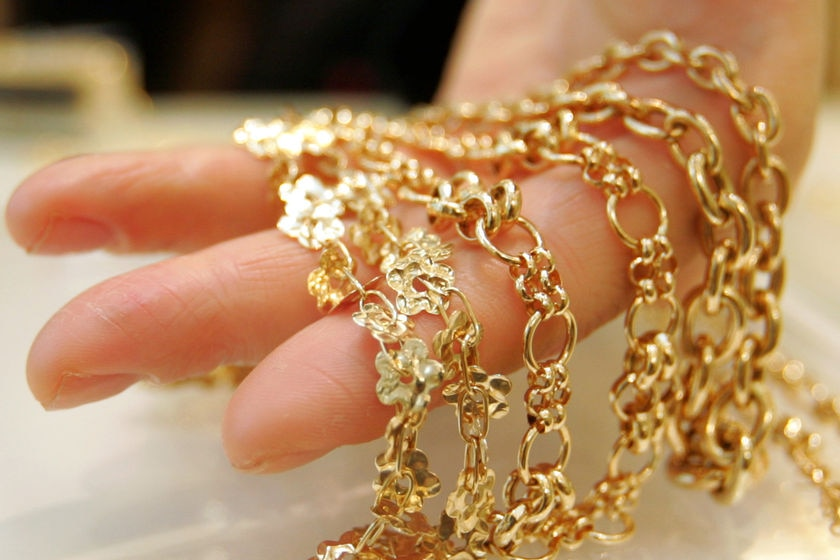 Gold jewellery draped over a  hand