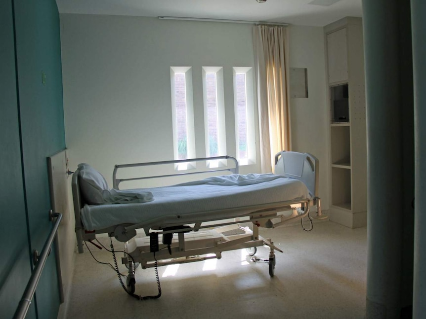 A room with am empty bed in it.