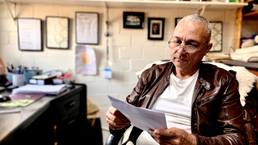 A man wearing a leather jacket and glasses looks at paperwork.