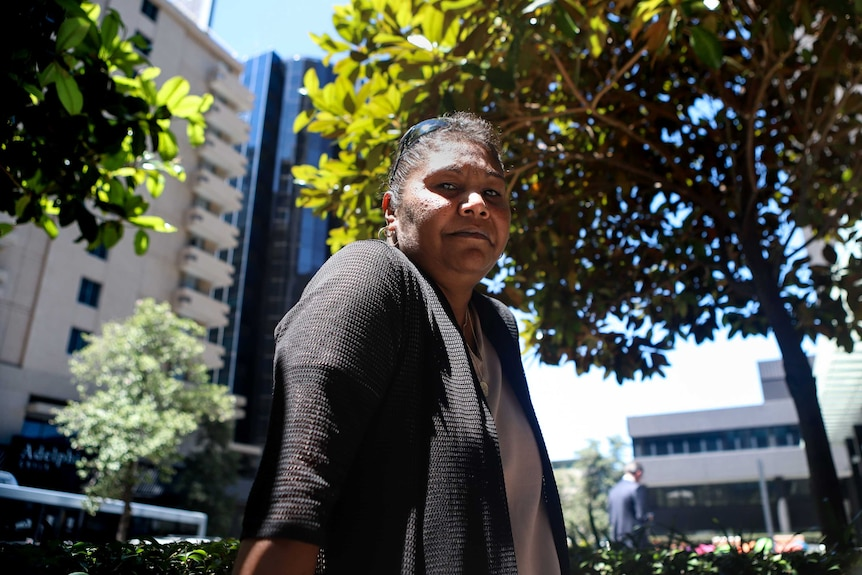 Adeline Parfitt, wearing black top, earrings and sunglasses on her head, stands underneath tree outside in city office setting