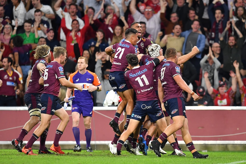 A group of Super Rugby AU players leap into each others arms after winning the competition final.