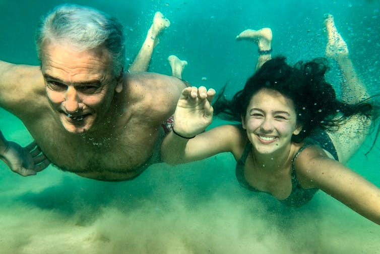 A father and daughter swim underwater
