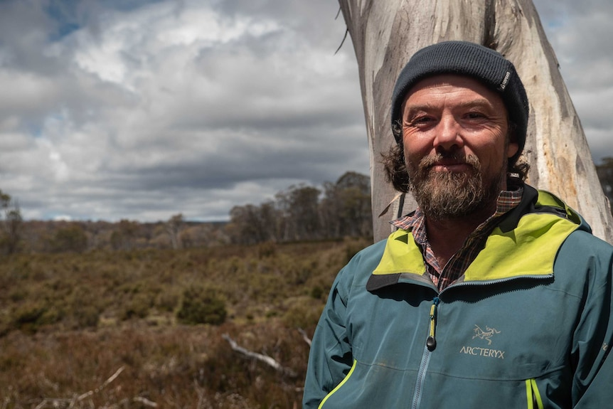 Dan Broun has a rugged beard, raincoat and beanie. He's standing in front of a white gum tree trunk with an open plain behind.