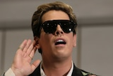 Milo Yiannopolous raises his hand to his hear during an event in Parliament House. He's wearing sunglasses despite being inside.