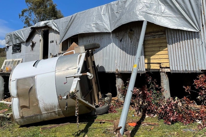 A trailer lies on its side in front of a corrugated iron building with a tarp on the roof.