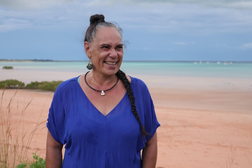Trudi stands on the beach, laughing.