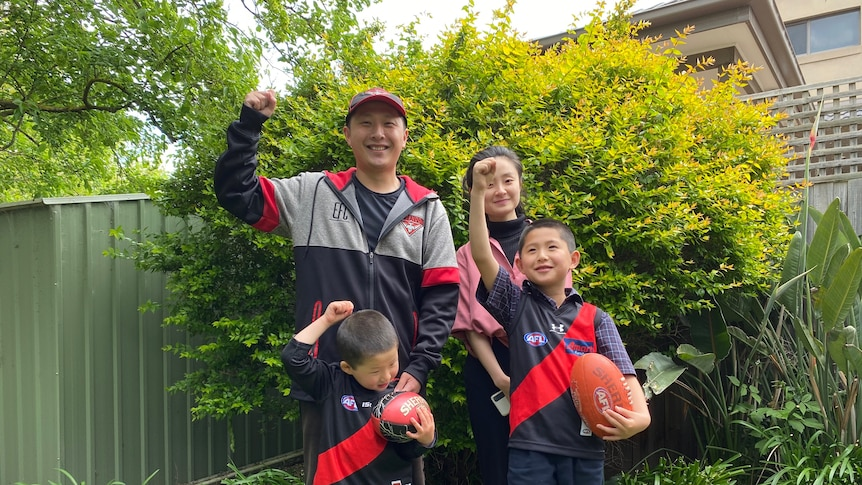 You look at a family in their garden raising their firsts while wearing Essendon Football Club merch.