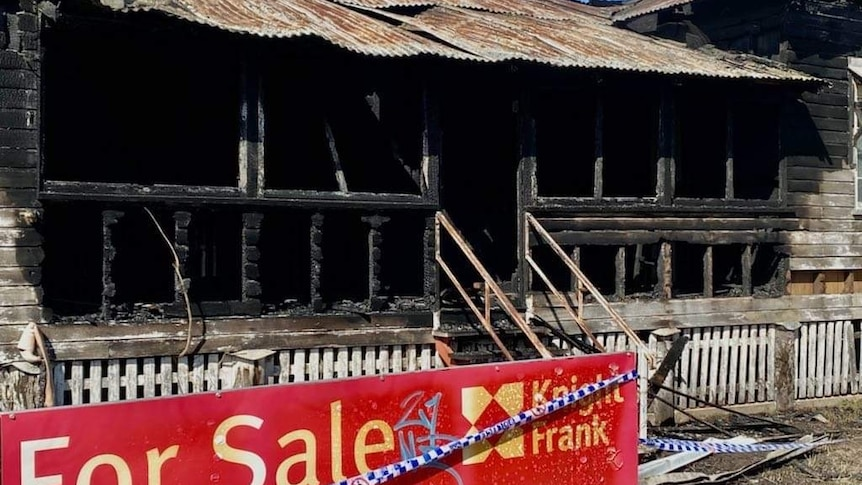 Burnt Queenslander home with a for sale sign and police tape