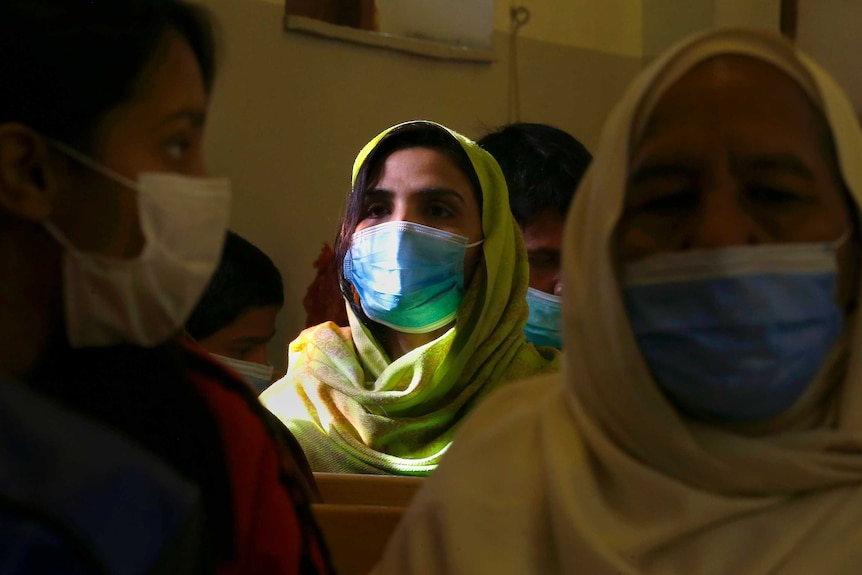 A Christian woman wears a face mask to protect against coronavirus during a prayer service