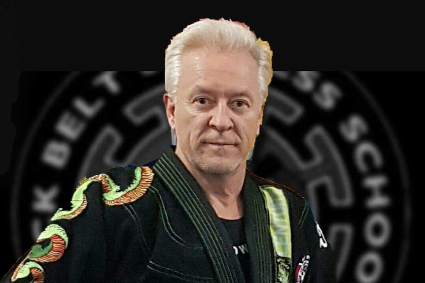 A man wearing a decorated martial arts uniform look into the camera.
