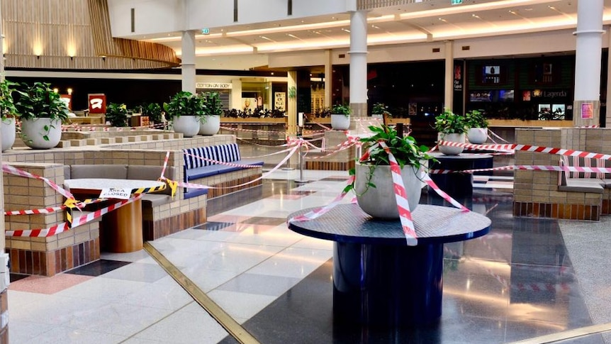 A shopping centre foodcourt is covered with red and white tape, yellow and black tape and a sign saying 'area closed'