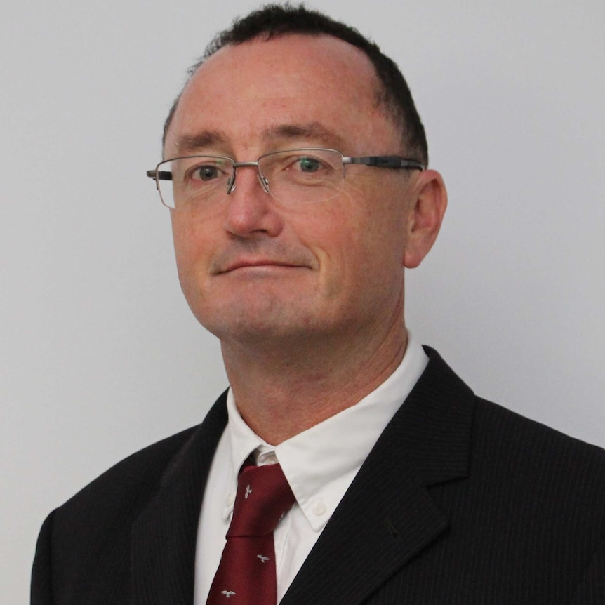 White bespectacled man wearing a suit and suit