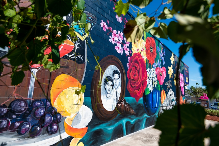 A brightly coloured mural of a still life scene, painted on the side of a building in a suburban area.