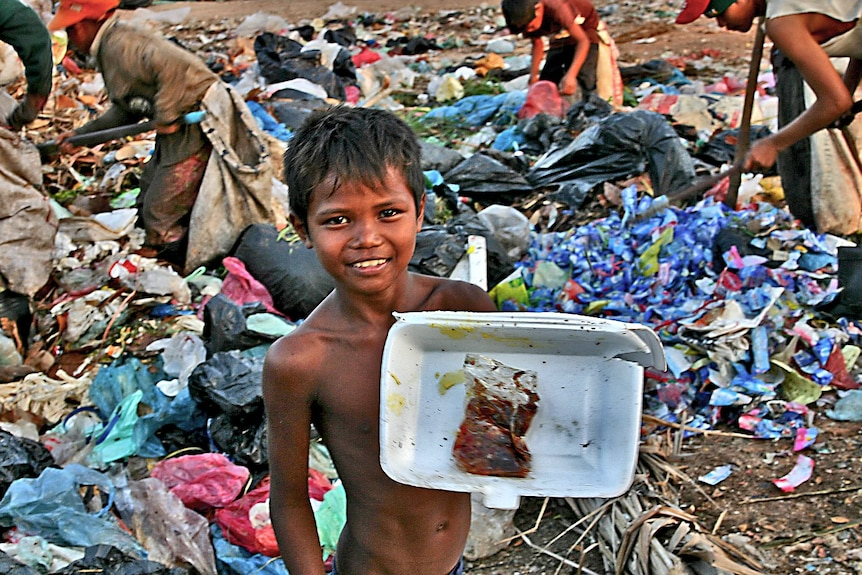 A boy shows off his find at a Cambodian rubbish dump