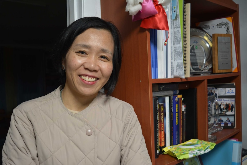 A South Korean woman with bobbed black hair and a beige coat leans against a bookcase and smiles.