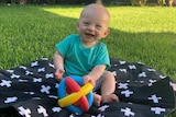 A baby sitting on a blanket laughing with a toy