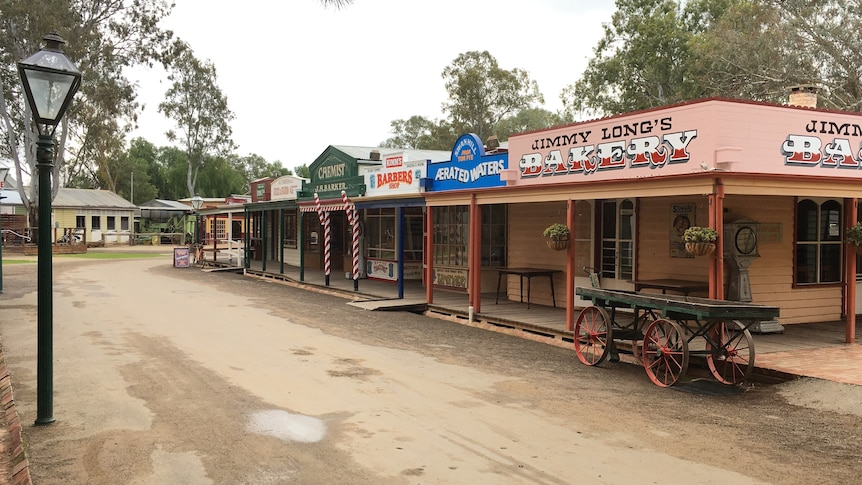 Dirt road with several old stores and an empty carriage.