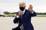 You view Joe Biden in a navy suit with a black face mask walking on an airport runway on an overcast day.