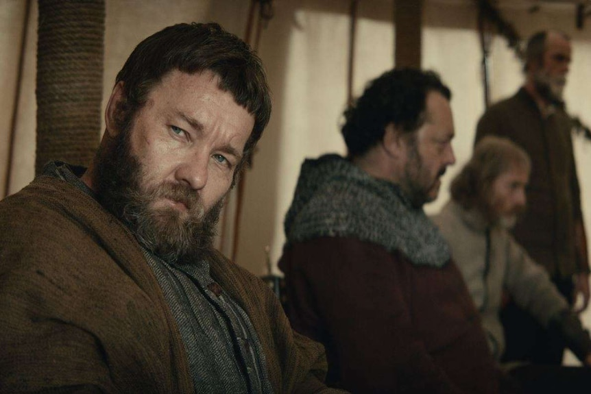 The actor Joel Edgerton in medieval garb and big beard, sitting in a tent with men dressed similarly in the background