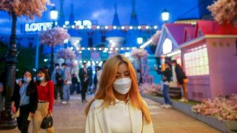 A young woman in a face mask walks through a street strung with fairy lights in Seoul.