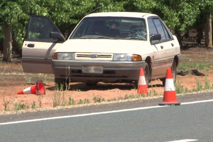A white Ford sedan with an open driver's door and a windscreen with a smash on the passenger side, on dirt beside a road.