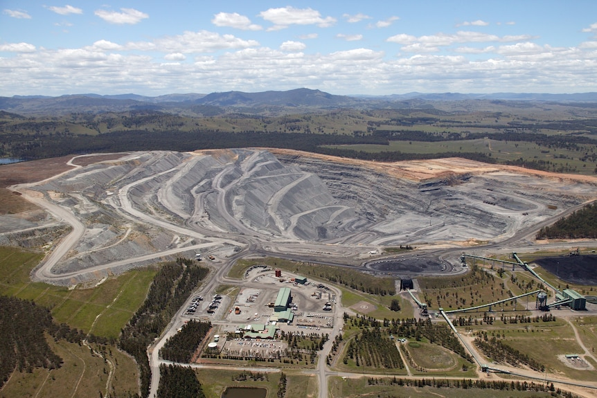 Aerial view of an open-cut coal mine. Treed hills and blue sky in distance.