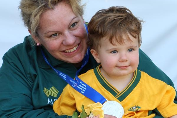 Natalie Smith with her toddler son Daniel on her lap showing her silver medal.