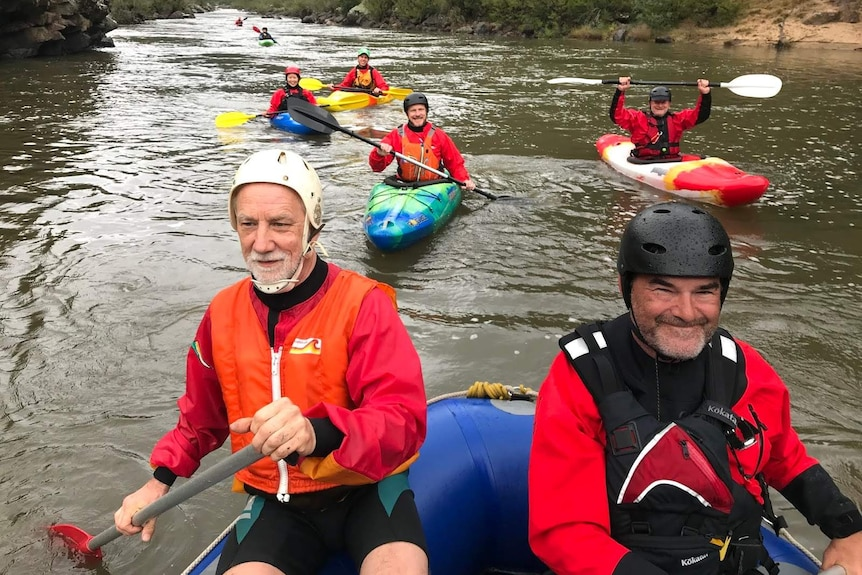 Kayakers smile as they paddle on a river.