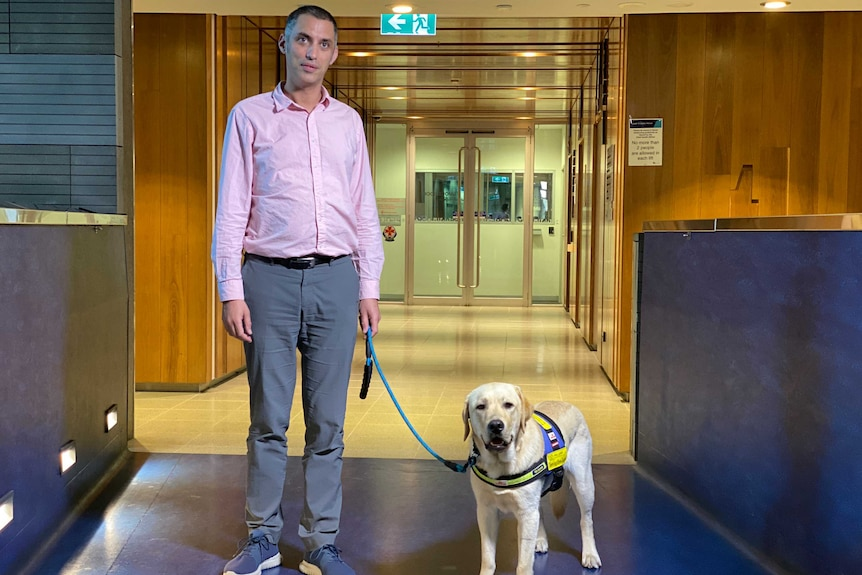 Dr Charles Alpren stands next to his dog Pippin.