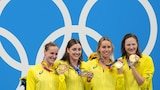 Four female swimmer on the medal podium after winning gold in the 4x100m relay
