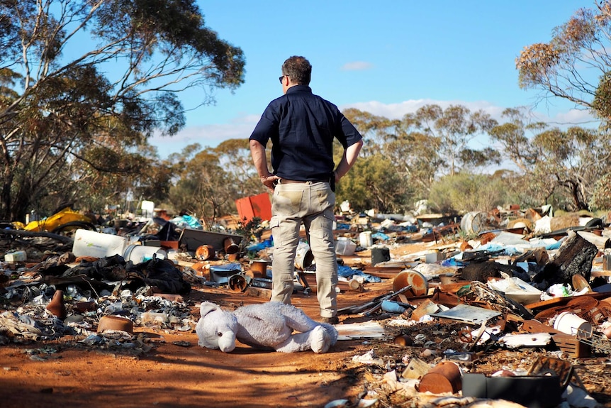 A man stands with his hands on his hips with his back to the camera surveying an area of scrub strewn with rubbish.