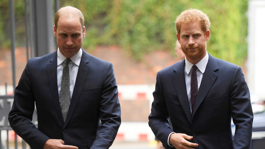 Britain's Prince William, the Duke of Cambridge, left, and Prince Harry wearing dark coloured suits.