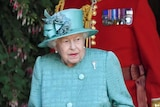 The Queen wears a blue suit and looks slightly to the right as she walks,with two men in military garb, one in red, one in black