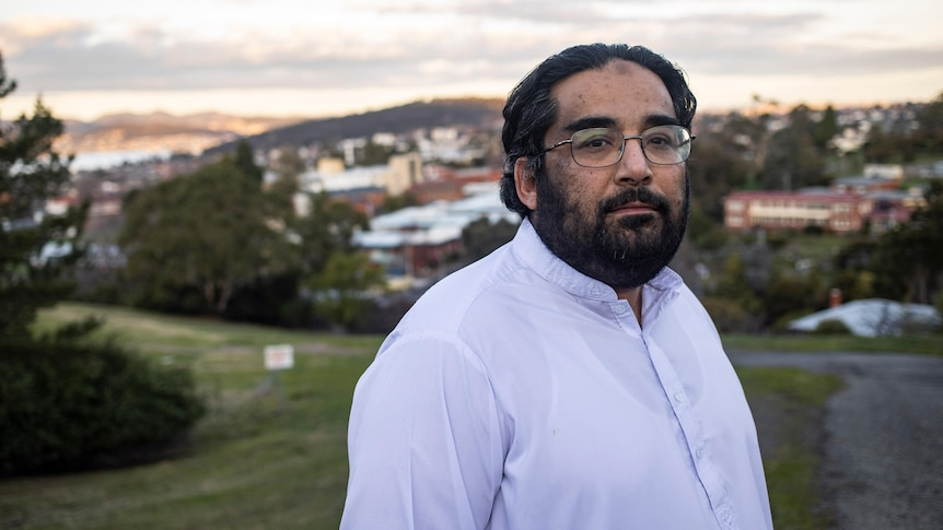 A bearded man wearing glasses stands atop a hill with houses behind him.