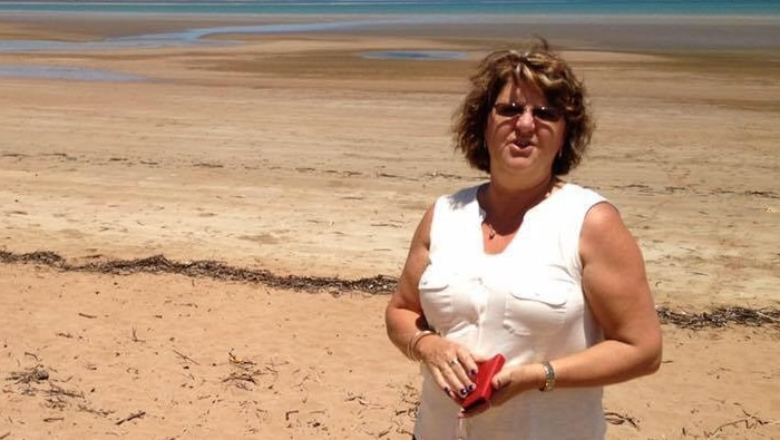 A woman standing on a beach holding her wallet.