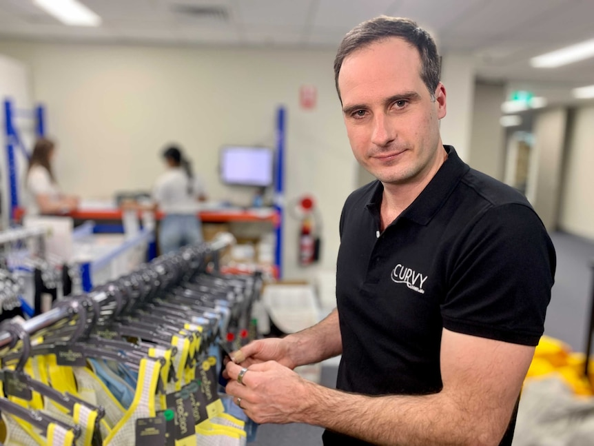 Curvy founder Wes Blundy inspects his company's bras with workers packing orders in the background.