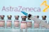 A needle balanced on a vial of the AstraZeneca vaccine