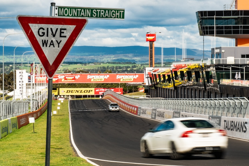 Give way Mountain Straight street signage in the foreground with cars driving along a race circuit.