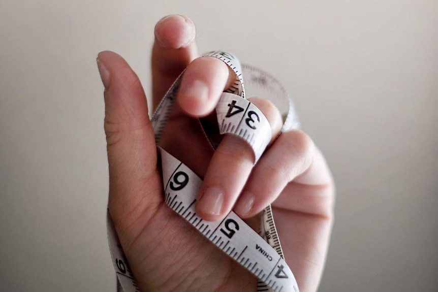 A hand holds a tangled tape measure.