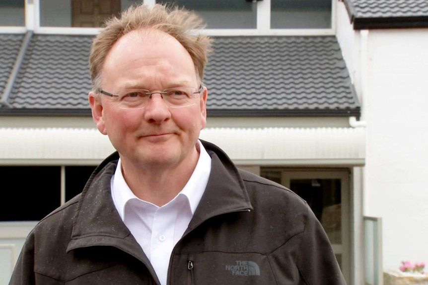 A balding man in glasses stands in front of a house