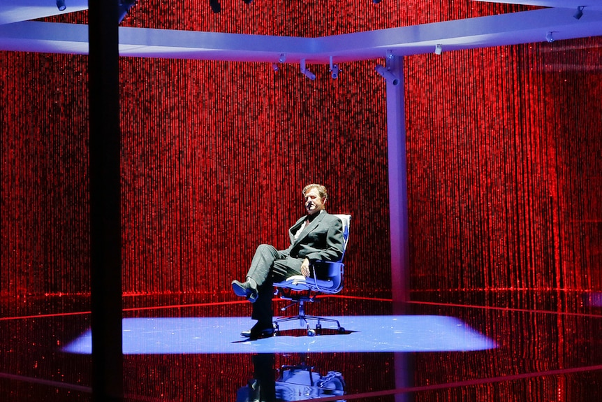 Darkened stage with backdrop curtain of red LED lights and and man sitting in chair under a blue-lit square pavilion structure.