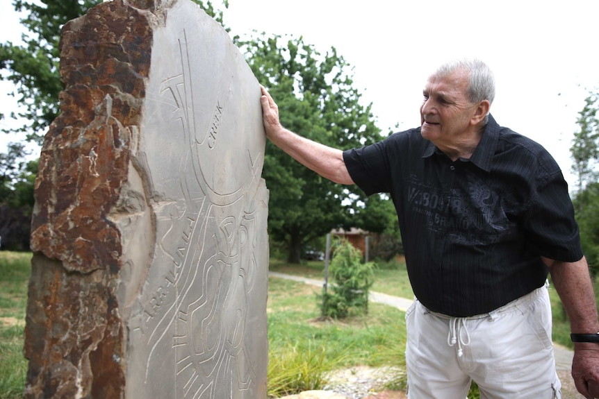 A man stoops to read the names on a stone memorial