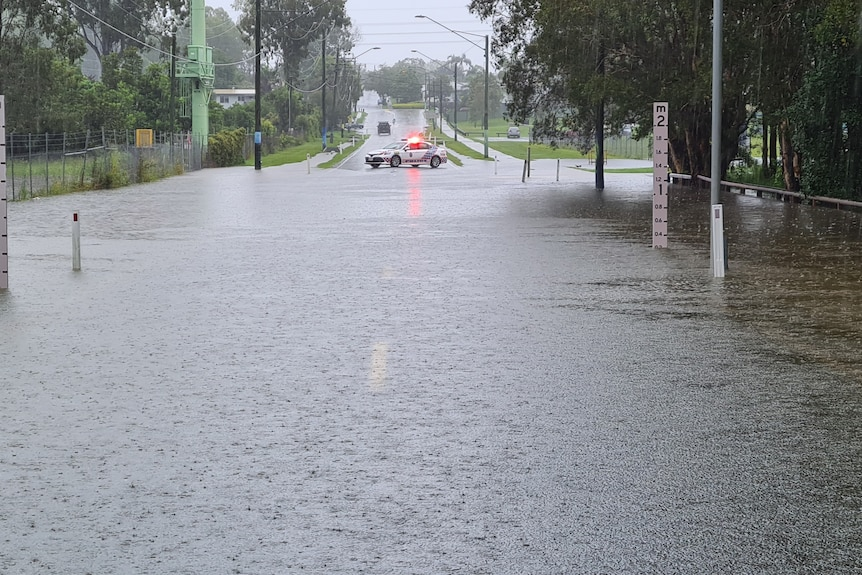 A police car blocks the road as floodwaters cover the road.