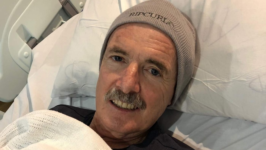 A man lies in a hospital bed with his blanket up to his neck and he is wearing a beanie.