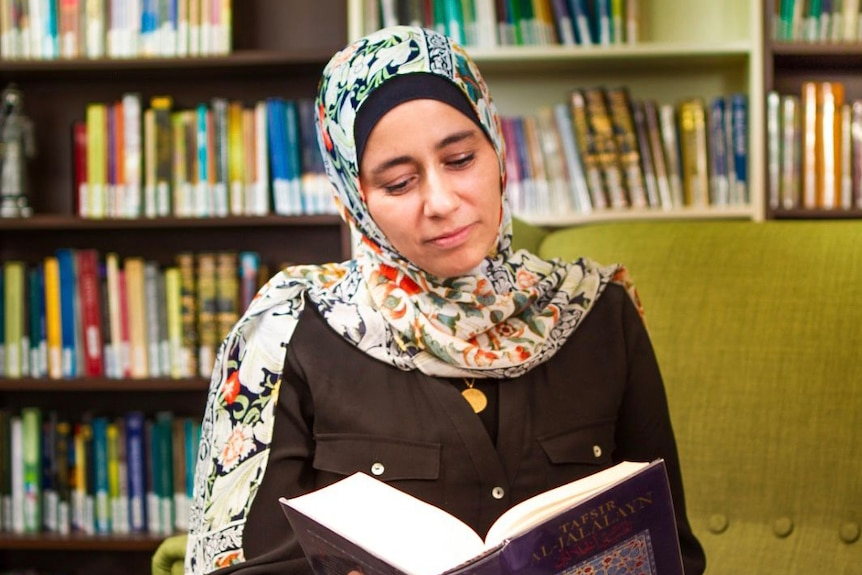 Qur'anic researcher Mouna Elmir wearing floral hijab and reading a book, with bookcases behind her.