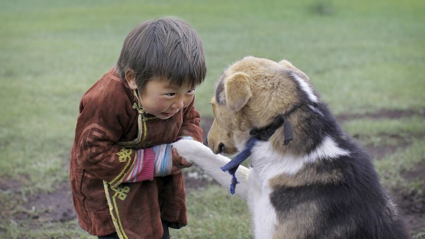 Boy from Mongolia with pet dog