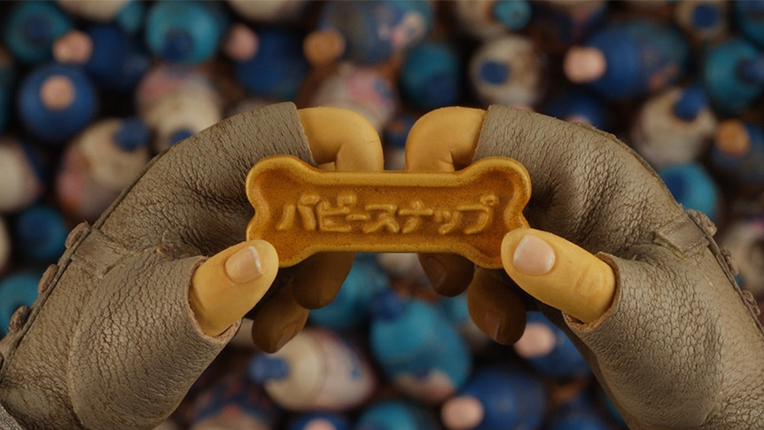 Colour close-up still of puppy snaps dog biscuit held in a puppet's leather glove wearing hand in stop-motion film Isle of Dogs.