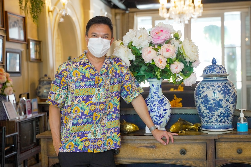 A Thai man in a bright shirt and face mask stands in hotel lobby