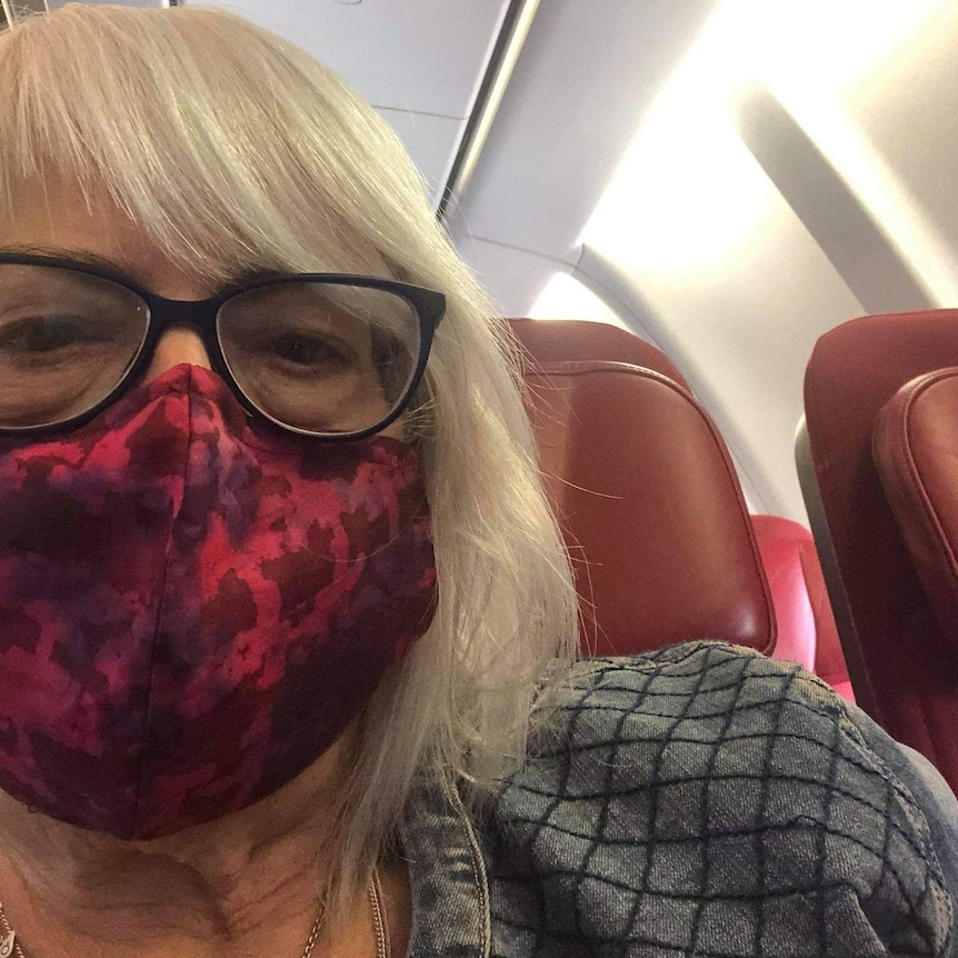 A selfie of a woman with glasses and wearing a mask sitting on an airplane