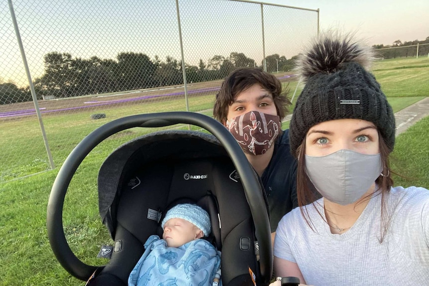 A baby in a pram with two parents wearing masks